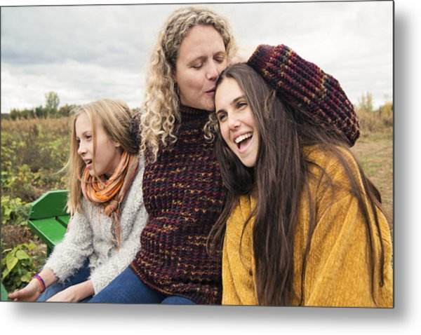Mother Kissing Teenage Daughter Strolling In Trailer In Field. Metal Print by Martinedoucet