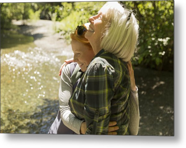 Senior Woman And Daughter Hiking Hugging By River Metal Print by Compassionate Eye Foundation/Steven Errico