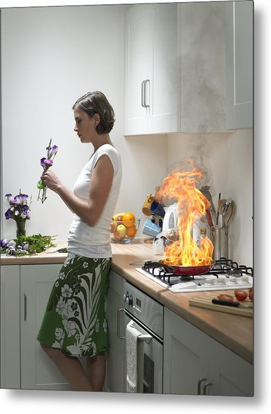 woman Leaning Against Kitchen Worktop Holding Flower, Frying Pan On Fire Behind Metal Print by Michael Blann