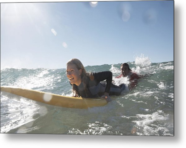 Young Man Being Towed In Sea By Young Woman On Surfboard, Smiling Metal Print by Anthony Ong