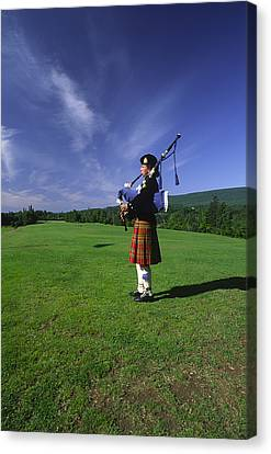 A Bagpiper At A Gaelic Mod Held Canvas Print by Michael Melford