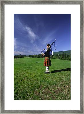 A Bagpiper At A Gaelic Mod Held Framed Print by Michael Melford