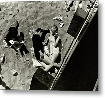 A Young Couple Lying On A Beach Metal Print