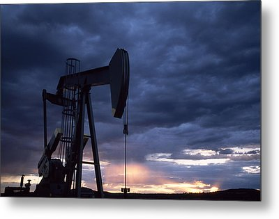 An Oil Rig Silhouetted At Sunset Metal Print by Joel Sartore