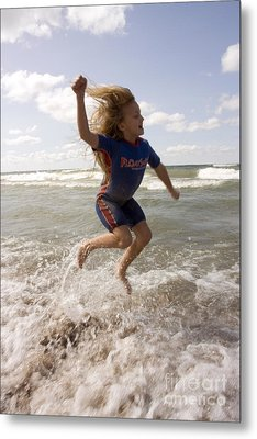 Young Girl Jumping Above Surf Metal Print by Christopher Purcell