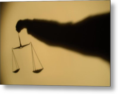 Shadow Of A Person's Arm Holding Out The Scales Of Justice Metal Print by Sami Sarkis