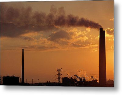 Silhouetted Smoking Chimney At Sunset Metal Print by Sami Sarkis