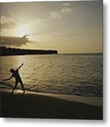 A Child, Silhouetted At Sunset, Throws Metal Print