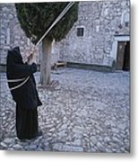A Nun Pulls On Ropes In A Courtyard Metal Print by Tino Soriano