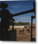 A Silhouetted Cowboy Watches Riders Metal Print