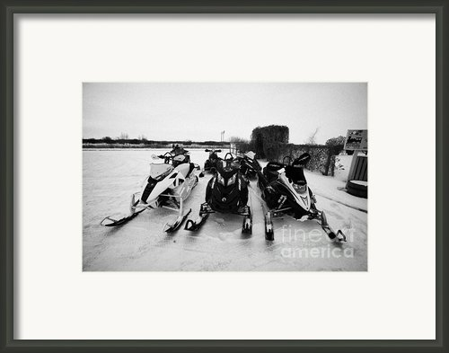 Snowmobiles Parked In Kamsack Saskatchewan Canada Framed Print By Joe Fox