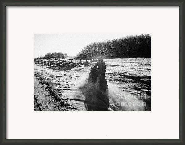 Man On Snowmobile Crossing Frozen Fields In Rural Forget Saskatchewan Canada Framed Print By Joe Fox