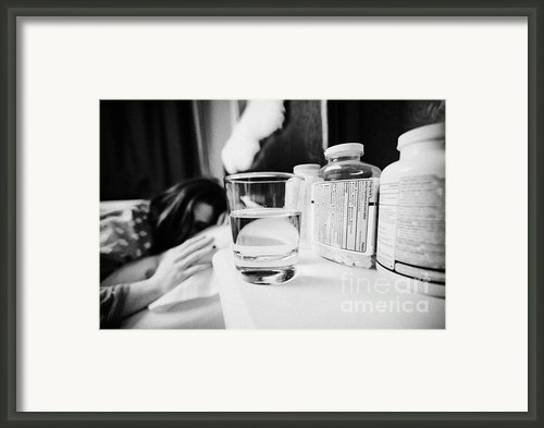 Glass Of Water And Bottles Of Pills On Bedside Table Of Early Twenties Woman In Bed In A Bedroom Framed Print By Joe Fox
