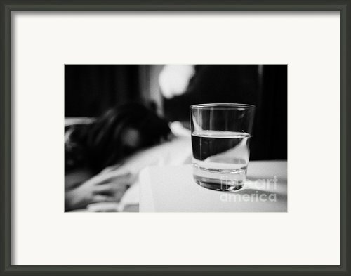 Glass Of Water On Bedside Table Of Early Twenties Woman In Bed In A Bedroom Framed Print By Joe Fox