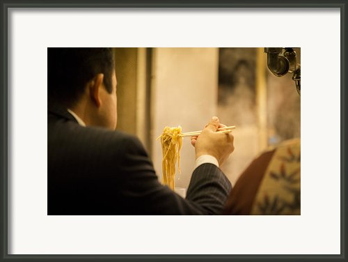 Man Eating Noodles In A Restaurant Framed Print By Ruben Vicente