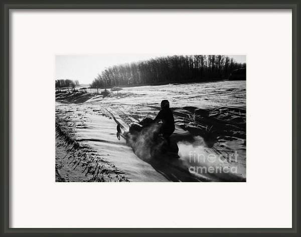 Man On Snowmobile Crossing Frozen Fields In Rural Forget Canada Framed Print By Joe Fox