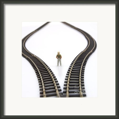 Figurine Between Two Tracks Leading Into Different Directions  Symbolic Image For Making Decisions. Framed Print By Bernard Jaubert