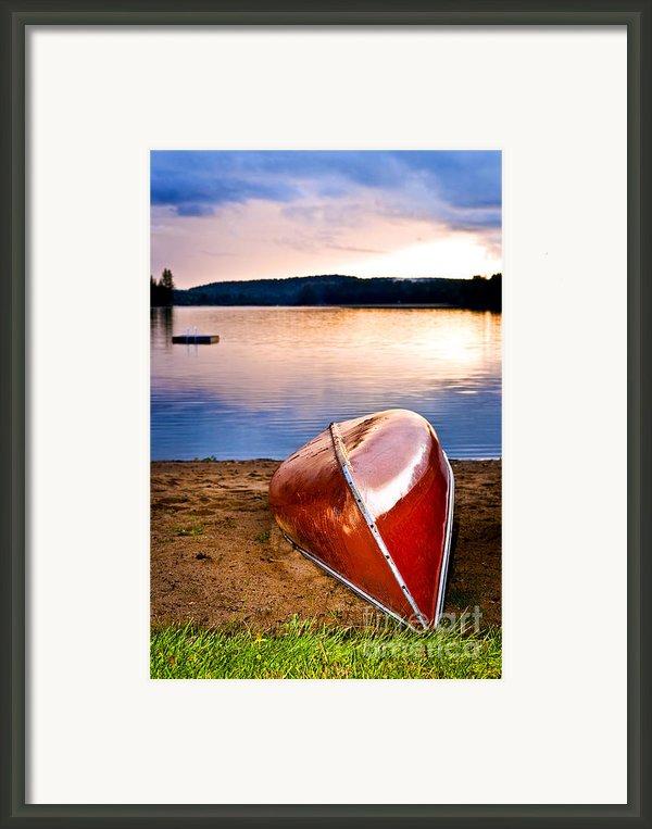 Lake Sunset With Canoe On Beach Framed Print By Elena Elisseeva