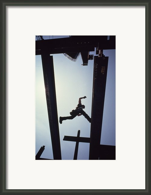 A Construction Worker Jumps From Girder Framed Print By Lynn Johnson