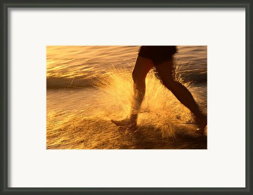 A Runner Splashing Through The Surf Framed Print By Phil Schermeister