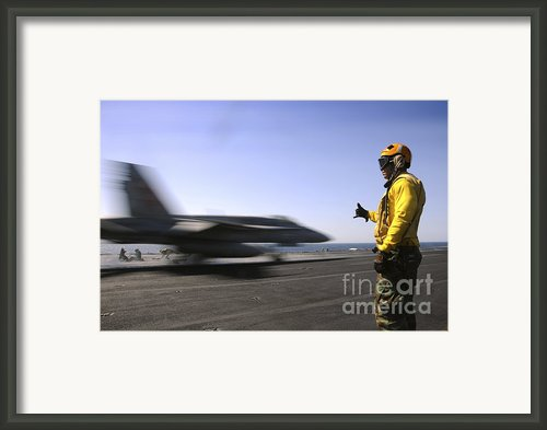 A Sailor Ensures An Fa-18c Hornet Framed Print By Stocktrek Images