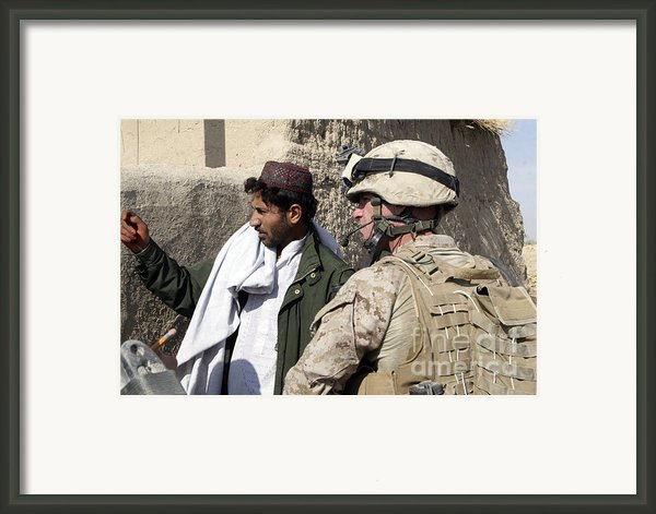 A Soldier Talks To A Local Villager Framed Print By Stocktrek Images