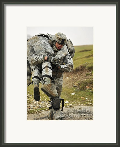 A Soldier Transports A Fellow Wounded Framed Print By Stocktrek Images
