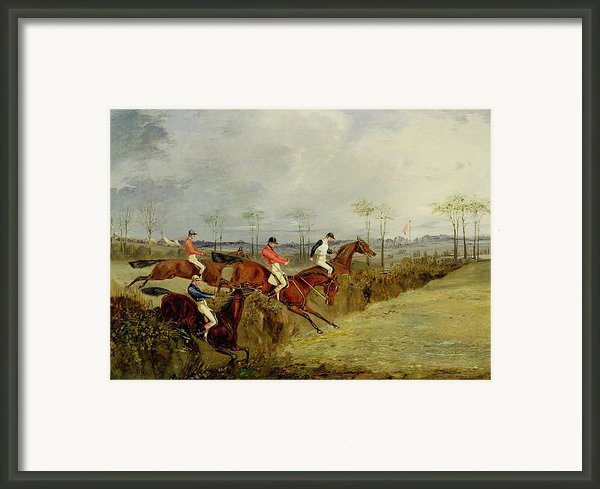 A Steeplechase - Taking A Hedge And Ditch  Framed Print By Henry Thomas Alken