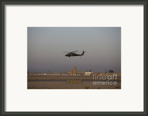 A Uh-60 Blackhawk Helicopter Flies Framed Print By Terry Moore