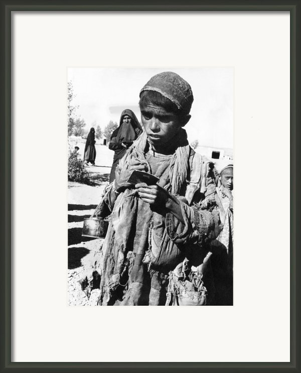 Afghan Youngster In A Unicef Feeding Framed Print By Everett