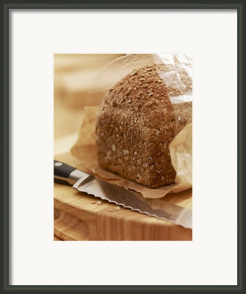 Close Up Of Knife And Loaf Of Bread In Wrapper Framed Print By Adam Gault