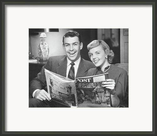 Couple Sitting On Sofa, Holding Magazine, (b&w), Portrait Framed Print By George Marks