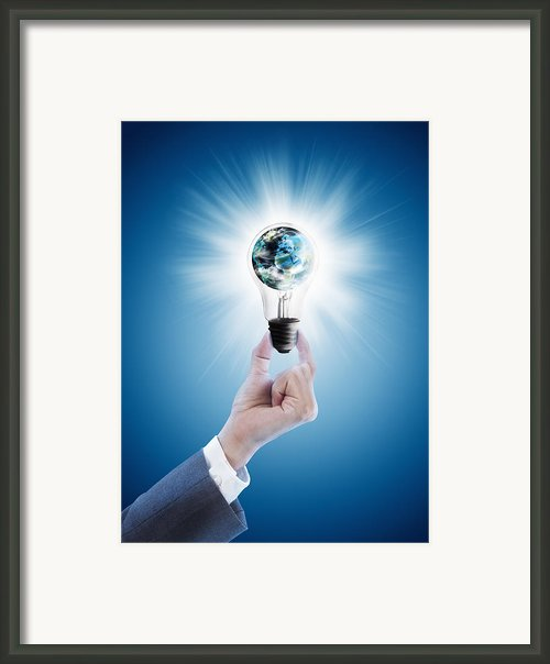 Hand Holding Light Bulb With Globe  Framed Print By Setsiri Silapasuwanchai