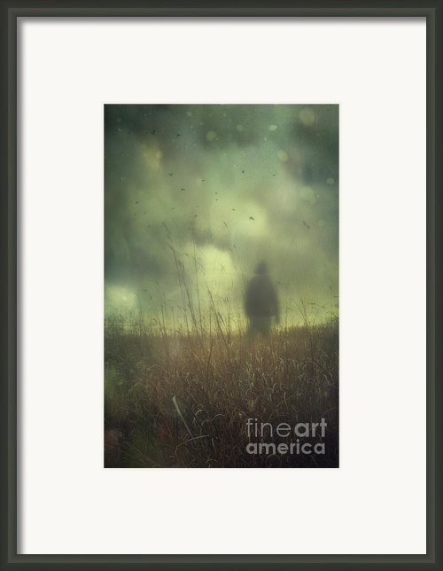 Hooded Man Walking In Field With Storm Clouds Framed Print By Sandra Cunningham