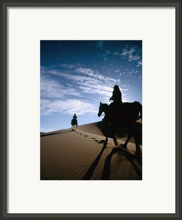 Horseback Riders In Silhouette On Sand Framed Print By Axiom Photographic