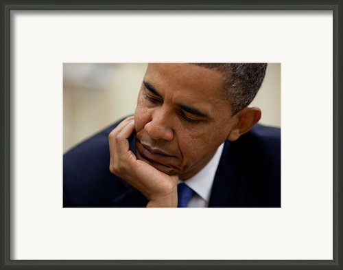President Barack Obama Reads A Document Framed Print By Everett
