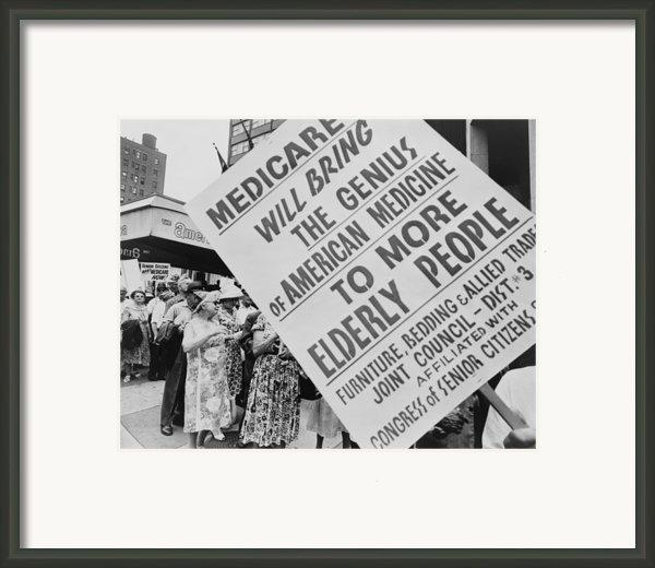 Retired Senior Citizens Carrying Framed Print By Everett