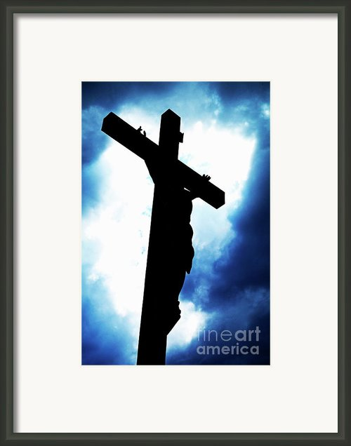 Silhouetted Crucifix Against A Cloudy Sky Framed Print By Sami Sarkis