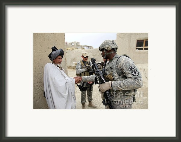U.s. Army Soldier Shakes Hands With An Framed Print By Stocktrek Images
