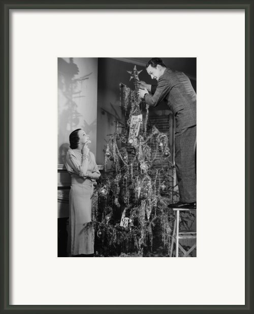 Woman Assisting Man Placing Star On Top Of Christmas Tree, (b&w) Framed Print By George Marks