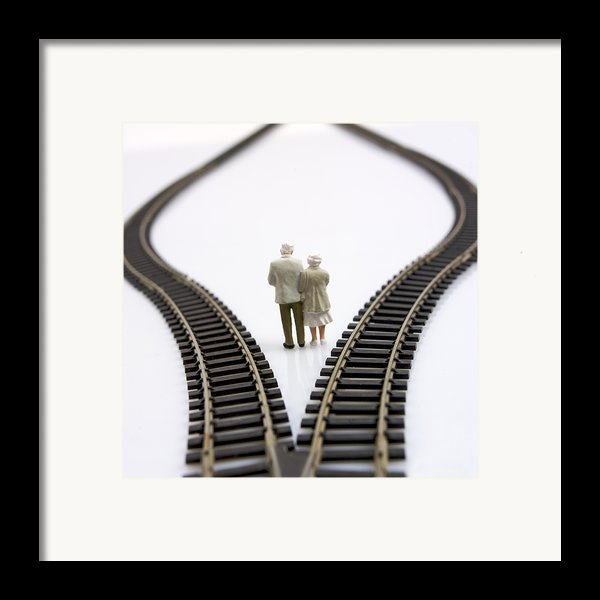 Figurines Between Two Tracks Leading Into Different Directions Symbolic Image For Making Decisions. Framed Print By Bernard Jaubert